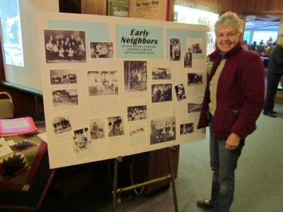 Photo of member Punky Scott standing in front of a history display at the OLHD booth in the Milwaukie Elks Lodge